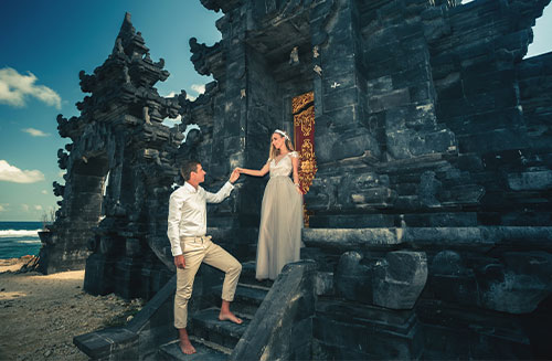 Portrait of happy couple near traditional gate. Traveling at Bali nusa duo. Honeymoon summer travel at Indonesia