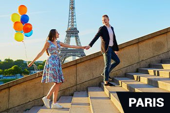 Romantic couple with colorful balloons near the Eiffel tower in Paris France walking up the stairs