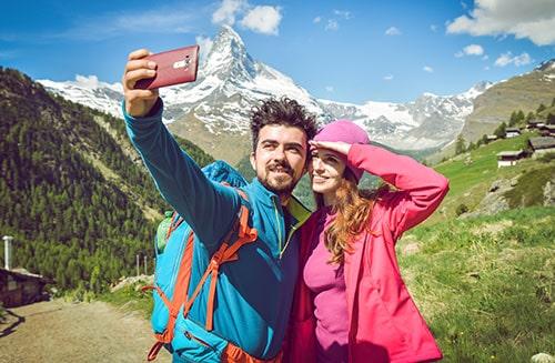 Tourist couple taking a selfie Boy holding the phone Beautiful scenic landscape in the back Matterhorn Switzerland 2017