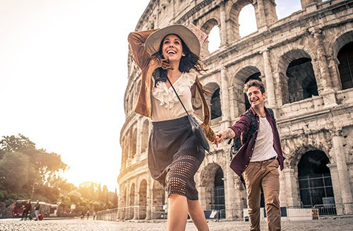 Young couple at the Colosseum Rome Happy tourists visiting italian famous landmarks